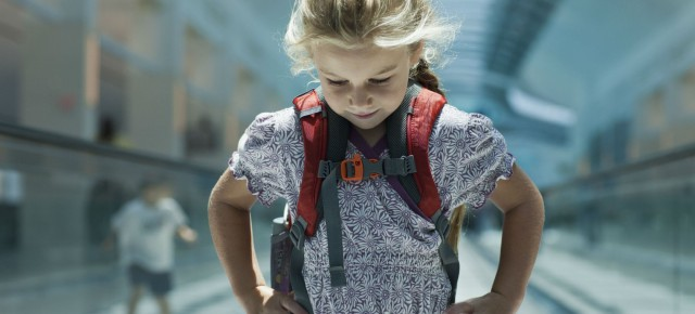 Un copil cară în spate un ghiozdan şi jumătate