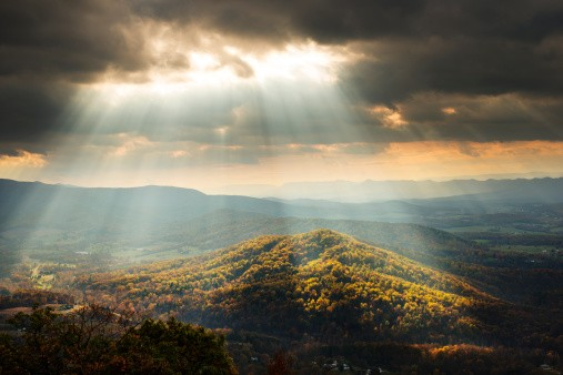 Sunlight Shining Through Clouds onto Hills