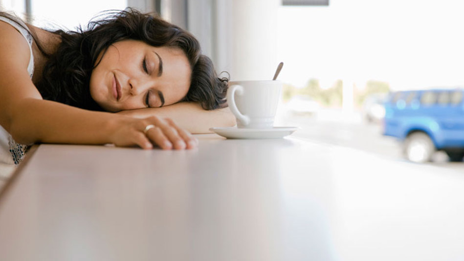 femeie epuizata doarme cafea masa