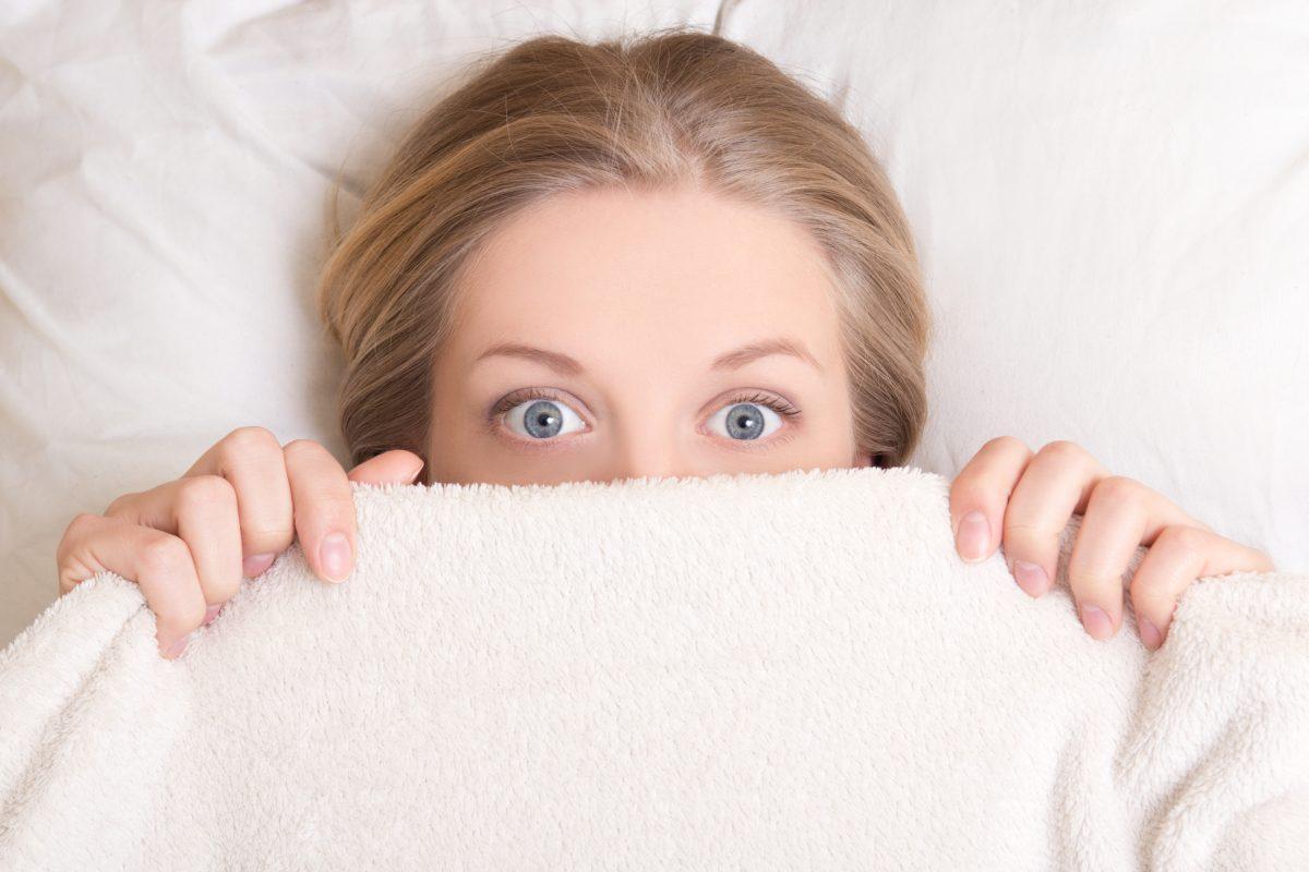 femeie speriata ingrijorata pat ochi deschisi