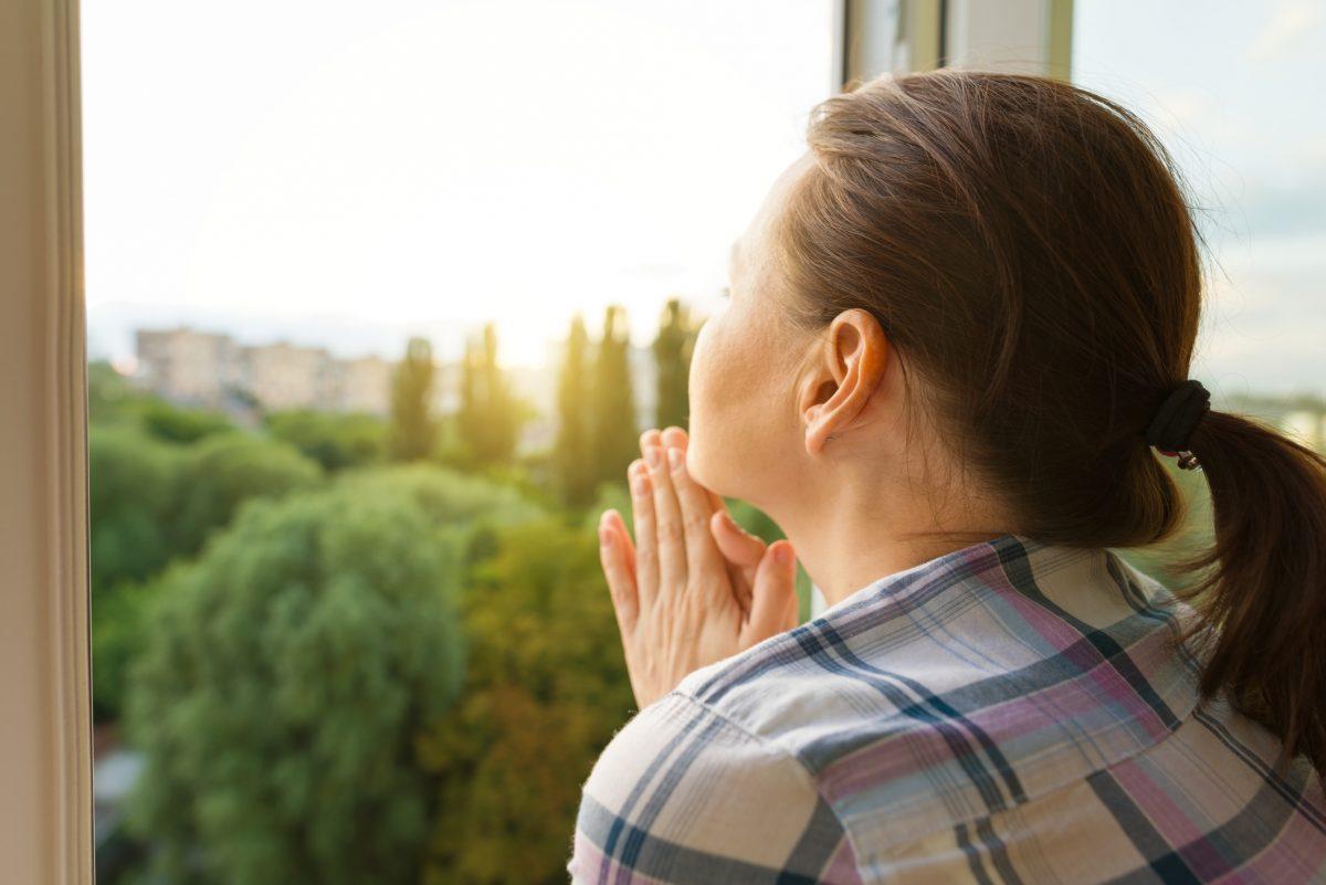 femeie se uita pe fereastra izolare