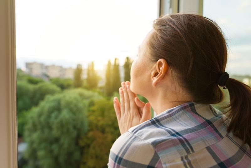 femeie geam speranta izolare